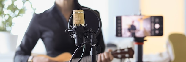 Woman sitting with microphone and holding ukulele in front of camera closeup freelance blogging
