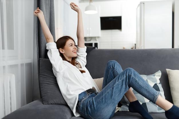 ソファの自由時間のアパートに手を上げて座っている女性。