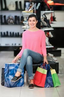 Женщина, сидящая с хозяйственными сумками