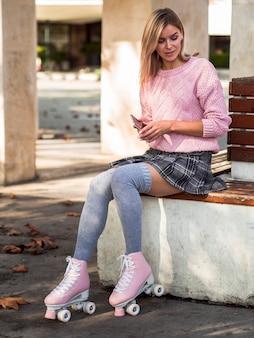Женщина сидит в носках и на роликовых коньках