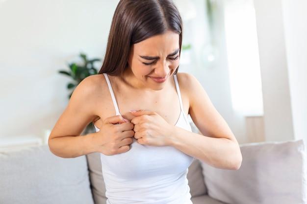 自宅で強い胸の痛みで座っている女性
