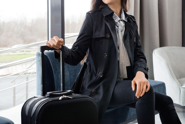 Woman sitting with suitcase in hotel lobby or in an airport lounge