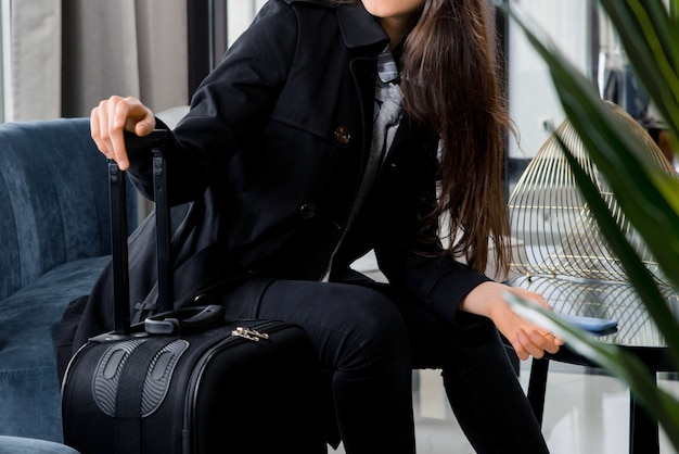 ホテルのロビーや空港のラウンジでスーツケースを持って座っている女性