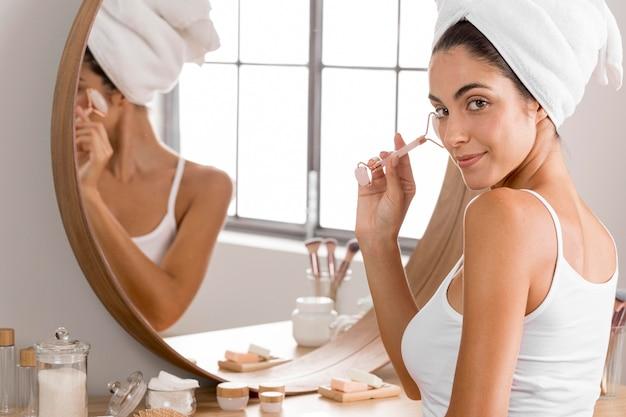 鏡の横にタオルで座っている女性