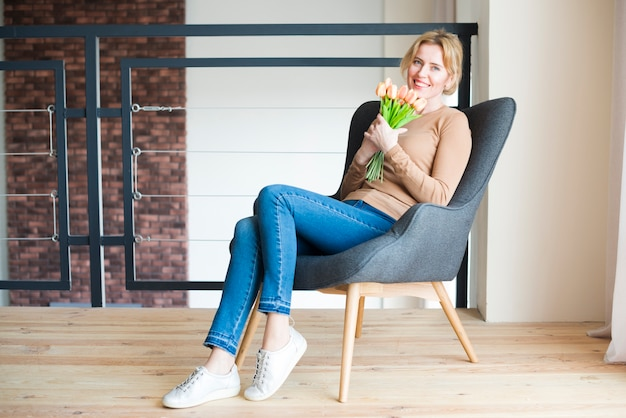 Woman sitting with tulips bouquet in armchair