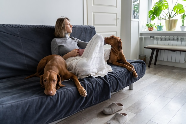 Woman sitting with two dog at home on sofa drinking tea