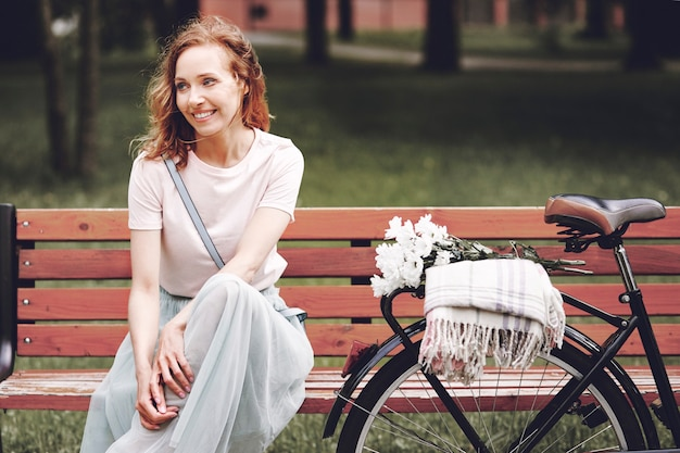 Woman sitting on wooden bench in park