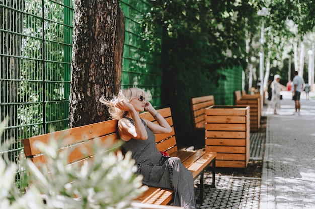 Woman sitting on wooden bench in summer park with green trees and sunny background with grass and