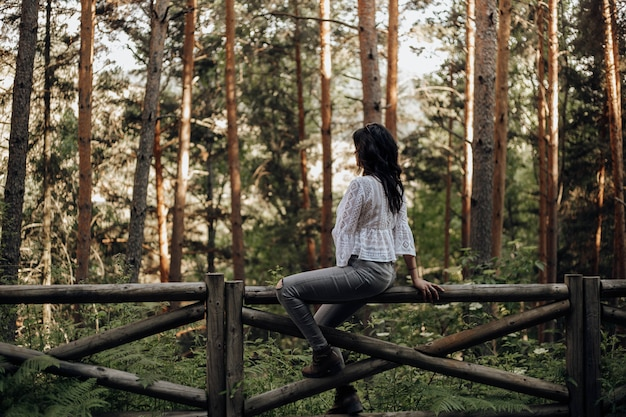 Woman sitting on a wooden fence in the forest among pine trees looking the nature