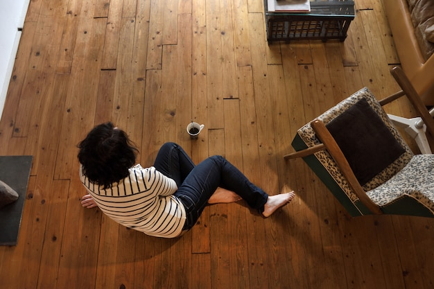 Woman sitting on the wooden floor