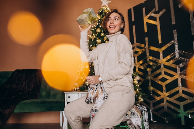 Woman sitting on wooden pony chair by the christmas tree