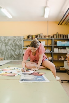 Woman sitting on workbench doing painting on canvas paper in workshop