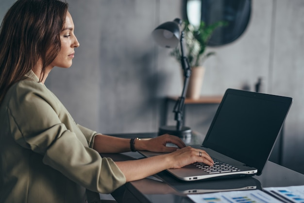 Woman sitting and working at workplace with laptop
