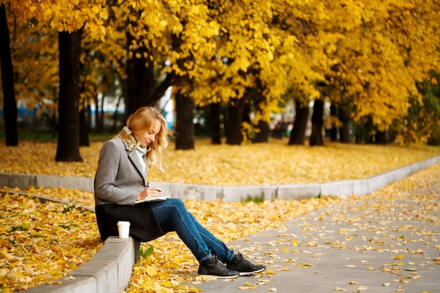 Woman sitting and writing something in her notebook in autumn park with golden trees