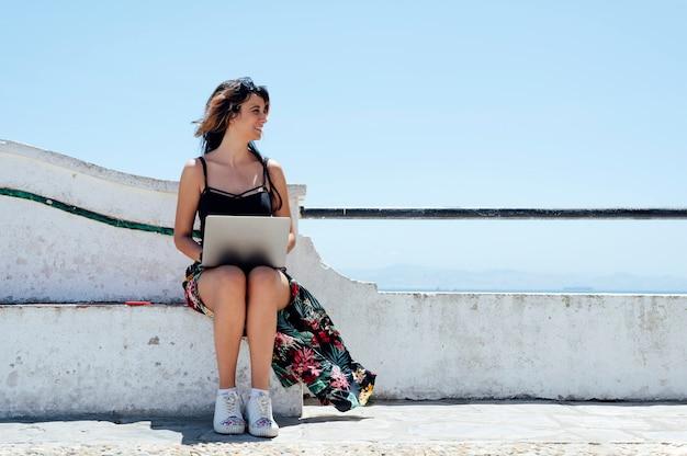 海の近くでノートパソコンで書く座っている女性