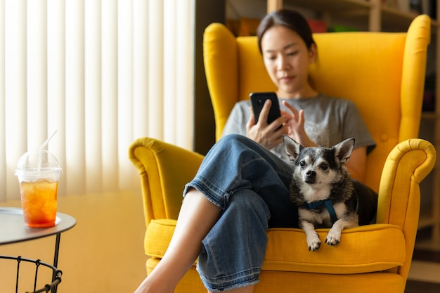 Woman sitting on yellow couch using cell phone with black chihua