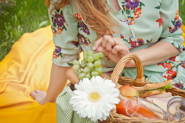 Woman sitting on the yellow cover with picnic basket with food, drinks and flower and holding bunch of grapes.