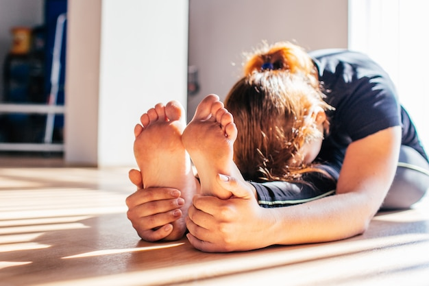 Woman size plus doing physical exercise and stretching legs on a mat