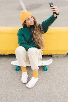 Woman on skateboard taking selfie