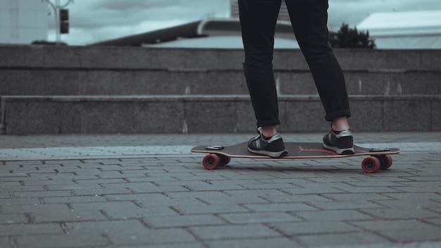 灰色の街でスケートボードをする女性のスケートボーダーの足