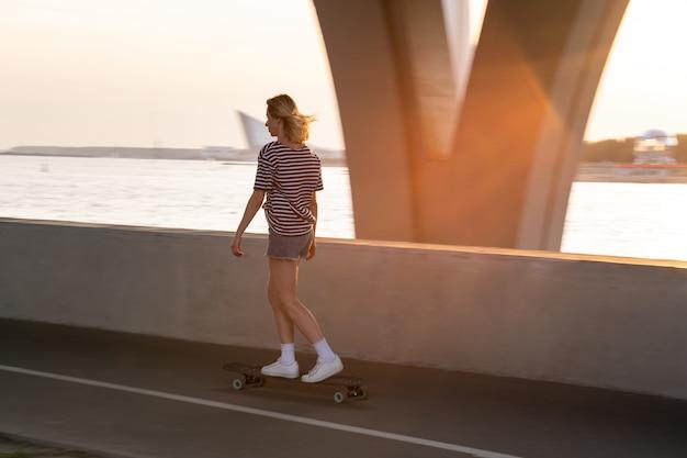 일몰 시 거리에서 롱보드를 탄 여성 스케이트보더 여성 롱보더는 강을 따라 혼자 타고