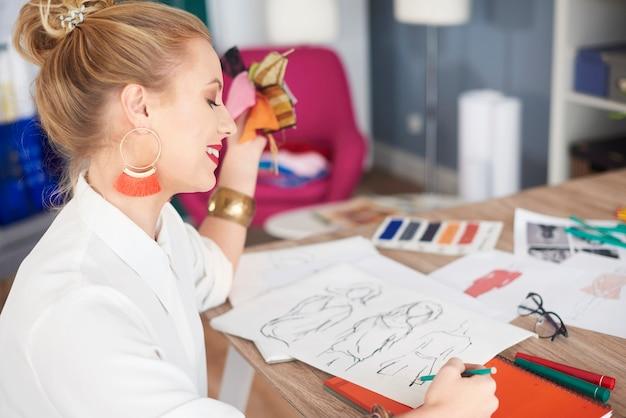 新しいコレクションのいくつかのデザインをスケッチする女性