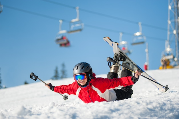 Woman in ski goggles lying with raised arms on snowy slope