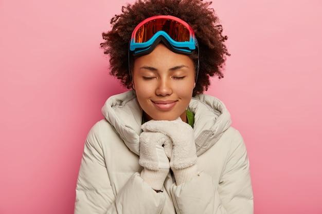 여자 스키어는 하얀 다운 패딩 코트, 흰색 부드러운 장갑을 입은 멋진 스노우 보드 시간을 즐기고 손을 턱 아래에 유지합니다.