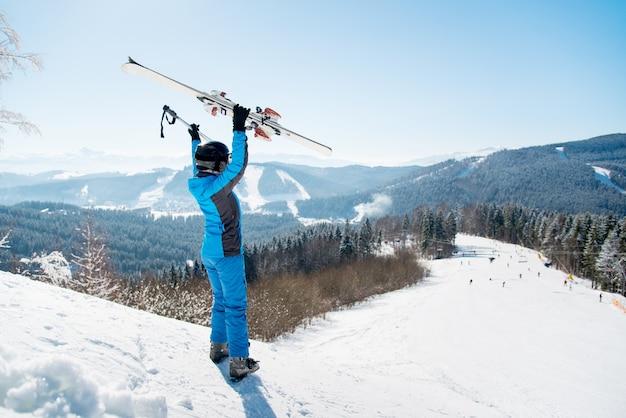 冬のスキーリゾートの斜面で女性スキーヤー