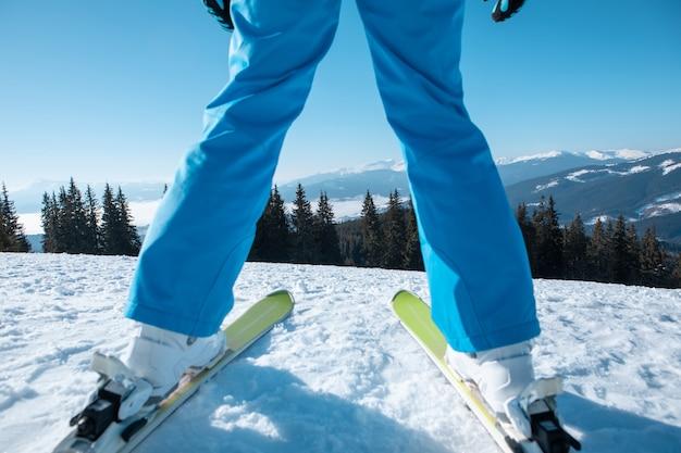 Портрет женщины лыжника с лыжами на вершине горы зимние каникулы