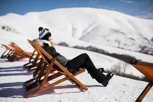 Woman skier relaxing in a lounge chair after skiing in the mountains in winter