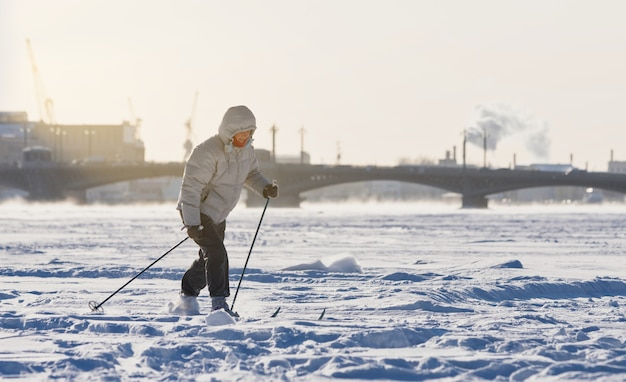 Woman skier riding on ice of frozen lake