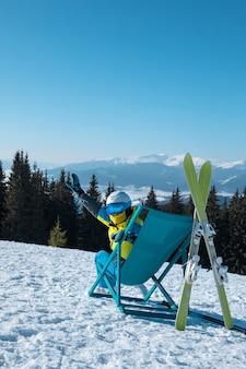美しい山々のパノラマビュースキーリゾートと椅子に座っている女性スキーヤー。冬休み