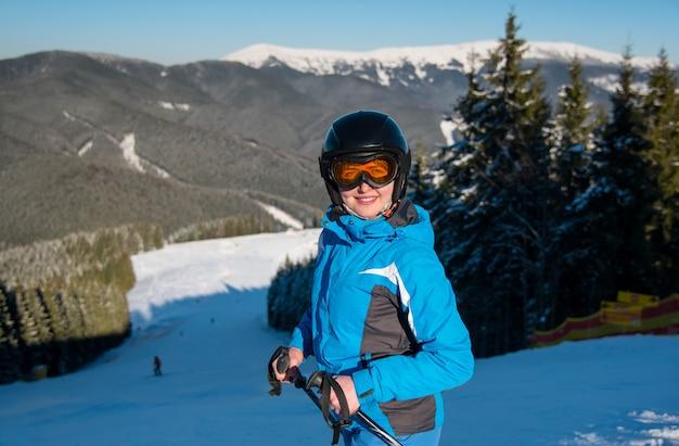 Woman skier on slope at ski resort in winter