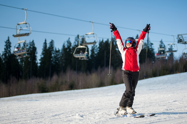Woman skier standing on snowy slope with hands raised up in sunny day with forest and blue sky in background.