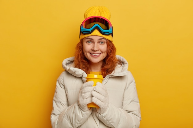 Woman skier wears warm winter outerwear, holds yellow takeaway cup with hot tea, wears cap and ski goggles, smiles pleasantly, models indoor.