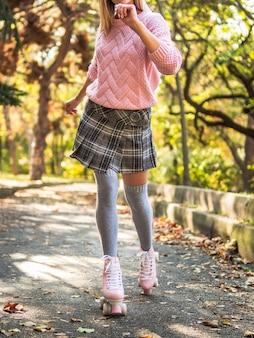 Woman in skirt and socks roller skating