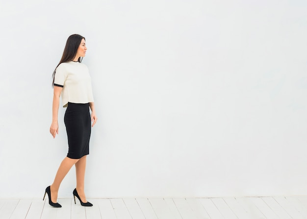 Woman in skirt suit standing on white wall background