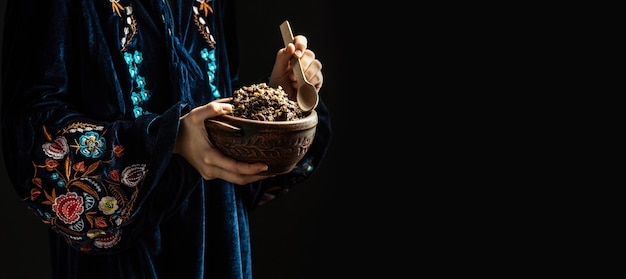 Woman in slavic holding bowl with traditional kutia