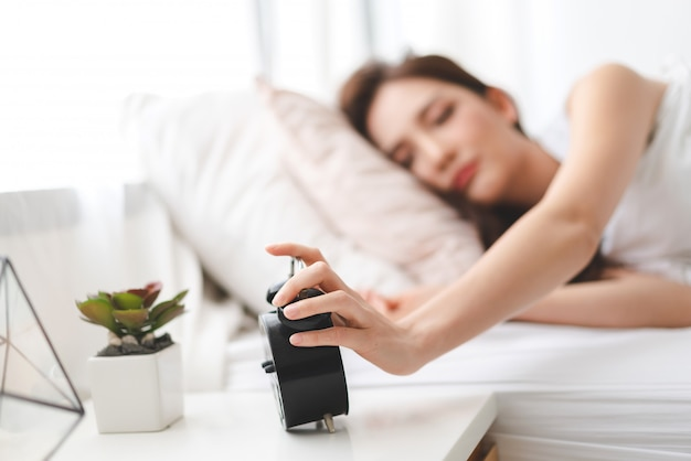 Woman sleeping and alarm clock in bedroom at home