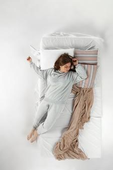 Женщина спит и отдыхает одна в своей постели, мечтая. вид сверху сверху