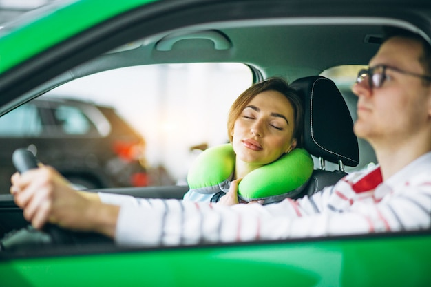 Woman sleeping in car on pillow and driving with her husband