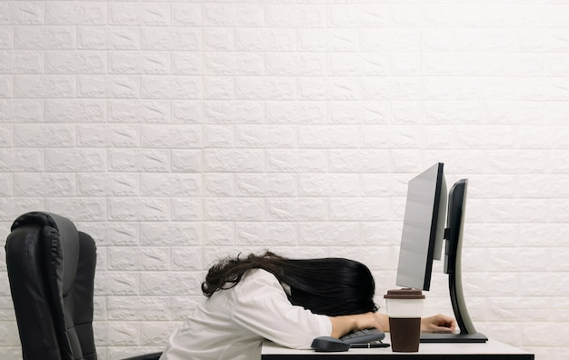 A woman sleeping on the desk computer screen