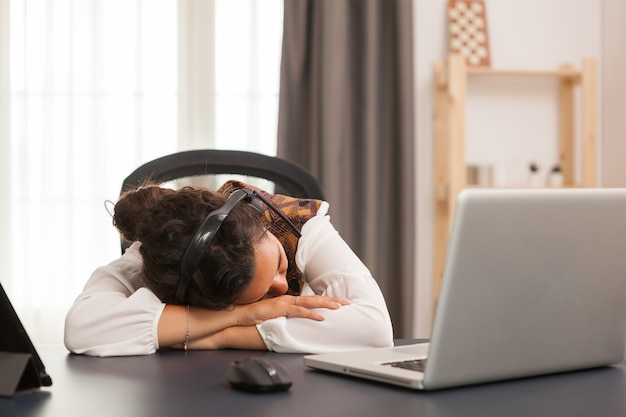Woman sleeping on desk while working from home office.
