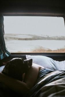 犬と一緒に車で寝ている女性