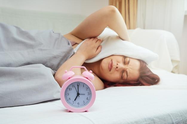Спящая в постели женщина недовольна ранним звонком будильника. женщина накрыла голову подушкой.