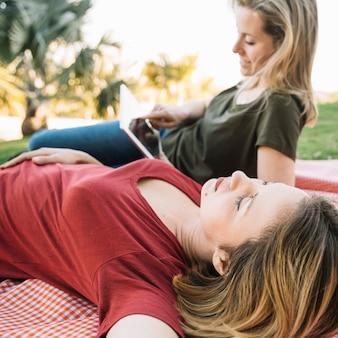 Woman sleeping near friend with tablet