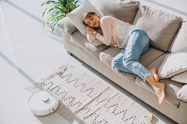 Женщина спит на диване, пылесос делает работу по дому