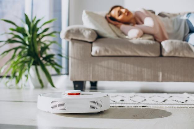 ソファで寝ている女性、家事をする掃除機