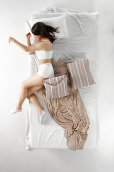 Woman sleeping and resting alone in her bed, dreaming. top view from above